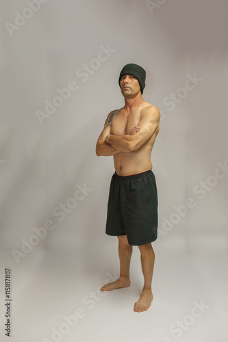Fotografie, Obraz  Muscular middle age man with tattoo standing with arms crossed facing left