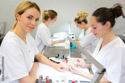 Young attractive beautician students practising during courses Wallpaper Mural