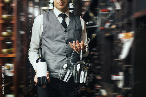 Close up of arms of skillful male sommelier standing in liquor store. He is holding a bottle of wine and two glasses. The man is smiling. Copy space in right side