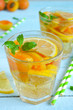 Cold, Summer lemonade with peach and apricot on a blue backgroun