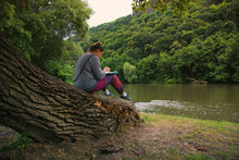 WOman Sitting On River Shore Reading Book