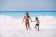 Young mother and her son enjoying in beautiful sunny tropical beach. Sea in the background.