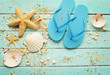summer sandals and seashells on wooden board