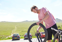 Cyclist Removing Wheel For Bicycle