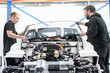 Engineers fitting windscreen to car in racing car factory