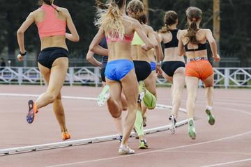 Fototapeta race of women athletes in stadium during athletics competitions