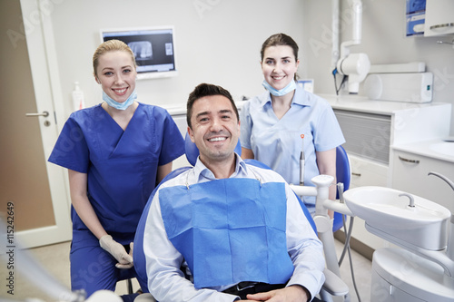 happy female dentists with man patient at clinic - Buy this