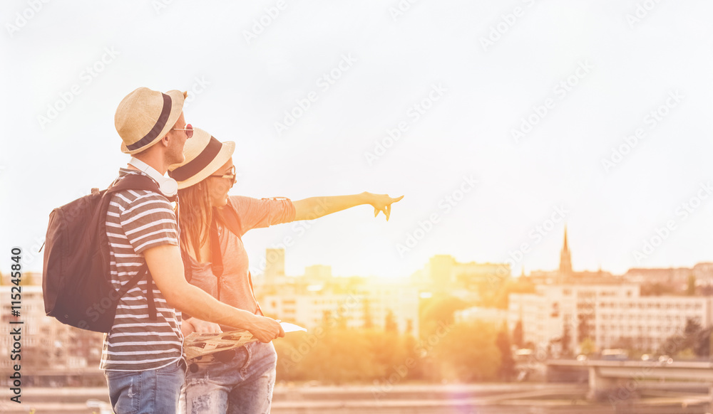 Fototapety, obrazy: Couple of young tourists consulting a city guide searching locations in the street and pointing - enjoying the city view
