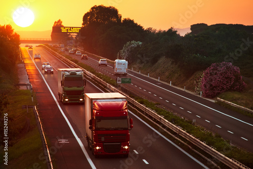 obraz dibond trucks in the highway at sunset