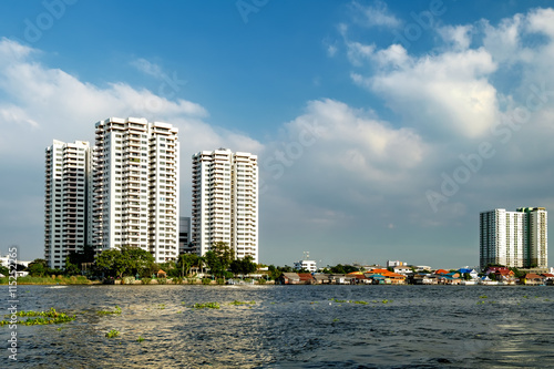 In de dag Milan Cityscape with modern building near the river in the afternoon at Chao Phraya River in Bangkok, Thailand