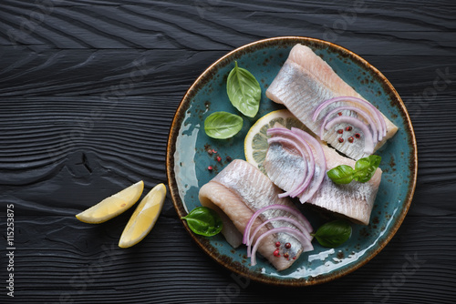 Photo  Top view of fresh herring fillet on a black wooden background