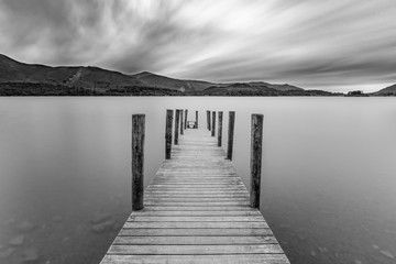 Długi drewniany pomost nad jeziorem Derwentwater z nastrojowymi chmurami dramatycznymi. Keswick, Kraina Jezior, Wielka Brytania.