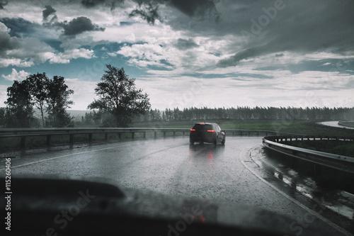 Spoed Foto op Canvas Stadion Drive car in rain on curve asphalt wet road