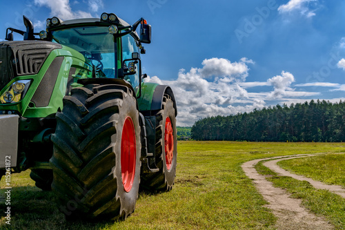 Part of the tractor standing in a field near the road.