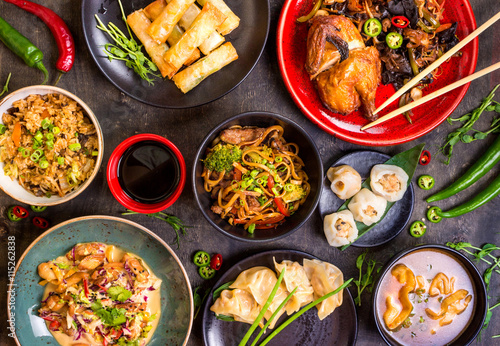 Poster Eten Assorted Chinese food set. Chinese noodles, fried rice, dumplings, peking duck, dim sum, spring rolls. Famous Chinese cuisine dishes on table. Top view. Chinese restaurant concept. Asian style banquet