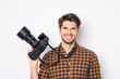 Young cheerful photographer holding camera  while working in stu