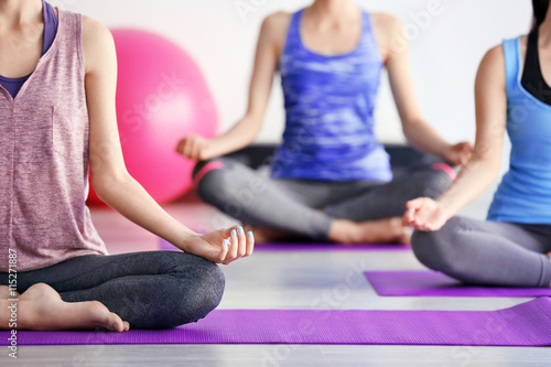 Spoed Foto op Canvas School de yoga Young women doing yoga in gym