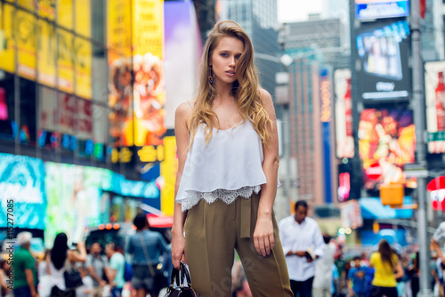 Plagát  Beautiful blonde fashionable model girl standing in New York City Time square wearing fashionable summer outfit with white t-shirt and holding leather bag