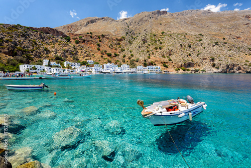 Fényképezés Small motorboat at clear water bay of Loutro town on Crete island, Greece