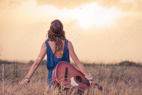 Fotomural Mujer joven hippy de estilo retro con la guitarra acústica en campo de trigo mirando al sol para encontrar la inspiración para la canción siguiente