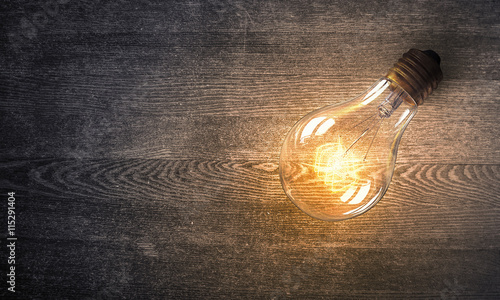 Photo  Light bulb on wooden surface . Mixed media