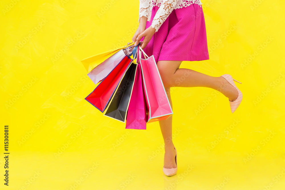 Fototapeta Woman with sexy legs holding shopping bags