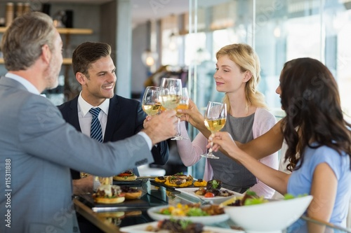 Fotografía  Business colleagues toasting beer glasses while having lunch