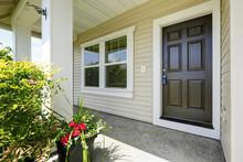 Open Porch With Concrete Floor, Column And Entrance Brown Door.