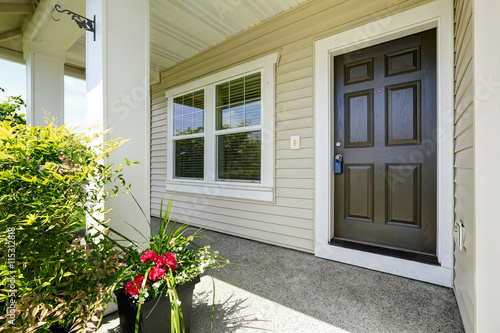 Photo Open porch with concrete floor, column and entrance brown door.