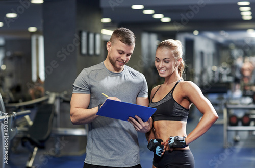 plakat smiling young woman with personal trainer in gym