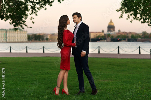 Fotografía  Young stylish couple standing at green grass near river in city