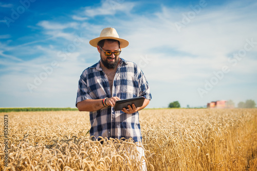 Photo Man on a wheat field holding a tablet.