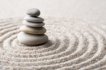 Fototapeta na wymiar Japanese zen garden meditation stone for concentration and relaxation sand and rock for harmony and balance in pure simplicity - macro lens shot