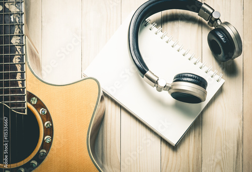 Fotografía  Blank note book binder with Golden music headphone and guitar for song writing