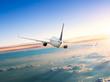 Leinwandbild Motiv Airplane flying above clouds in dramatic sunset