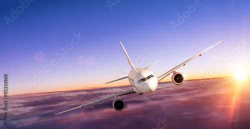Foto Airplane flying above clouds in dramatic sunset