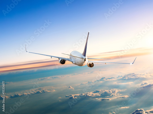 Airplane flying above clouds in dramatic sunset Fototapet