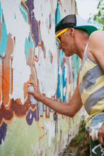 Senior Hipster Man Painting A Graffiti On A Wall With Spray