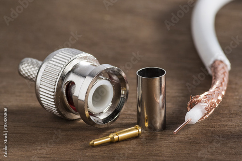 Photo  BNC connector for transmitting high-frequency signal and a piece of shielded cable on the wooden background
