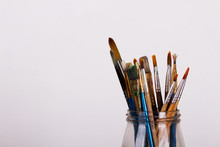 Paint Brushes In A Pot Against A White Background