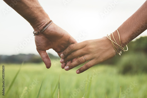 Loving couple holding hands in a field