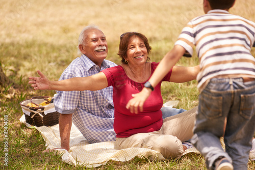 Photo  Grandparents Senior Couple Hugging Young Boy At Picnic