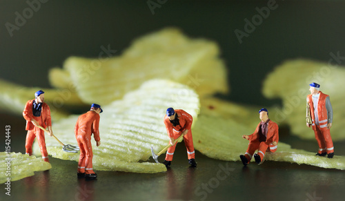 Fotografie, Obraz  Miniature worker are working with potato chips  Color tone tuned macro photo