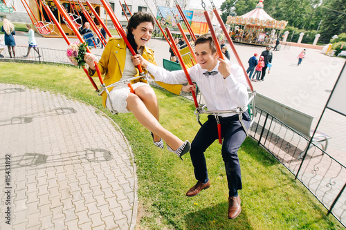 Poster Amusementspark Emotional newlyweds laughing while riding on high carousel in amusement park. Expressive wedding couple at carnival.