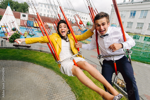 Emotional newlyweds screaming while riding on high carousel in amusement park. Expressive wedding couple at carnival.