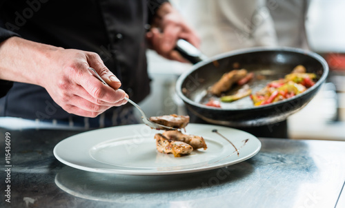 Koch richtet Essen auf Teller an in Restaurant oder Hotel Küche