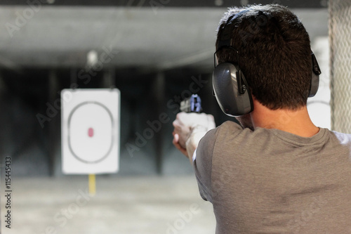 Cuadros en Lienzo man firing usp pistol at target in indoor shooting range