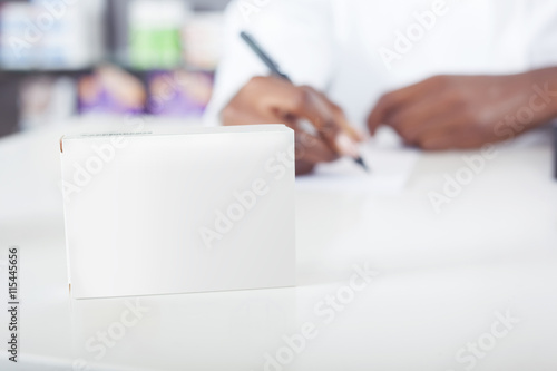 Valokuva  Black pharmacist or doctor writing with tablet package with copy space