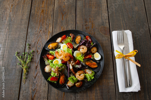 Portion of grilled seafood salad with cutlery on wood. Served with knife and fork and rosemary on white napkin salad wirh grilled seafood on wooden table