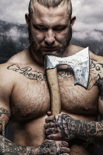 Photo  Portrait of tattooed bearded shirtless male with axe.